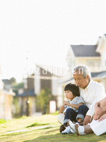 芝生に座る祖父と孫
