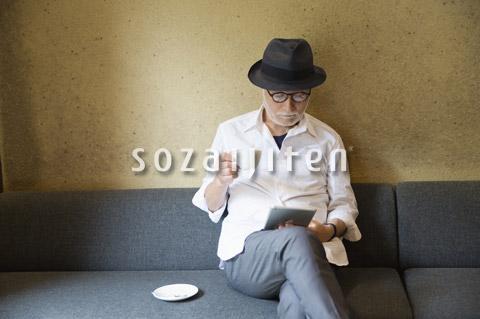 コーヒーを飲みながらタブレットPCを見るシニア男性