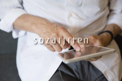 タブレットPCを操作するシニア男性の手元