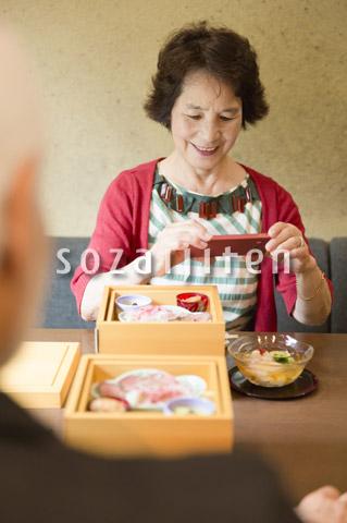 料理の写真を取るシニア女性
