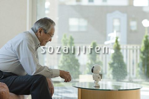 コミュニケーションロボットで遊ぶシニアの男性