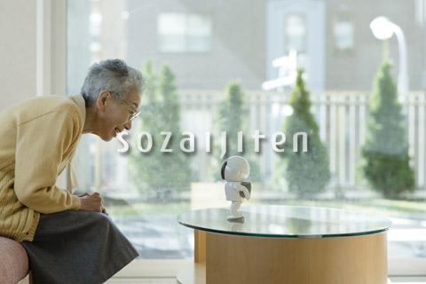 コミュニケーションロボットで遊ぶシニアの女性