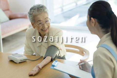 血圧を測るシニアの女性