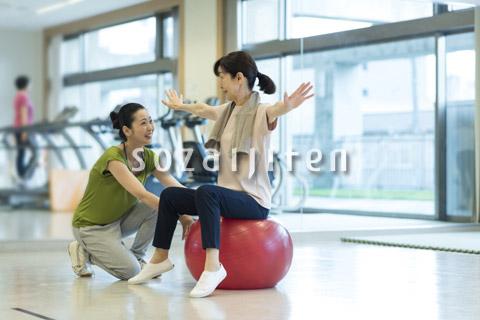 バランスボールで運動するシニアの女性