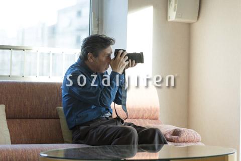 カメラをいじるシニアの男性