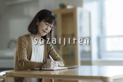 エンディングノートを書くシニアの女性