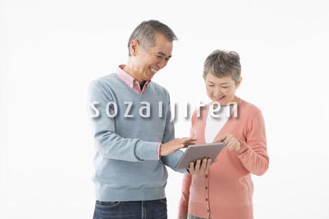 タブレットを操作するシニアのカップル