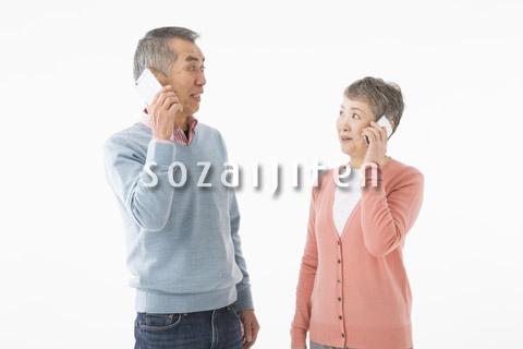 スマートフォンで話すシニアのカップル