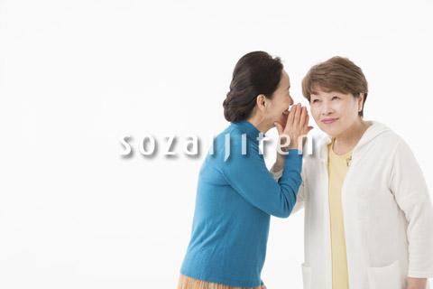 ひそひそ話をするシニアの女性2人