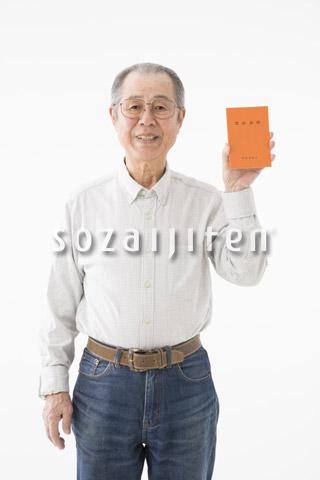 年金手帳を示すシニアの男性