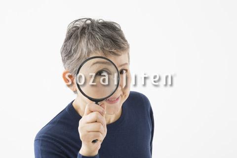 ルーペを覗き込むシニアの女性