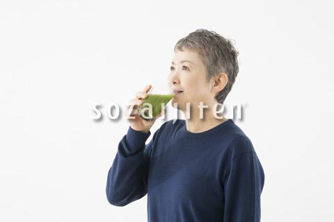 青汁を飲むシニアの女性