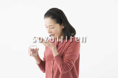薬を飲むシニアの女性