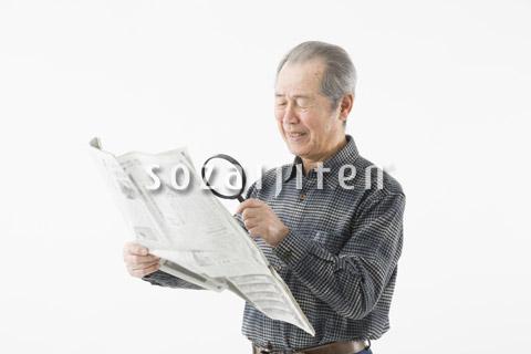 ルーペで新聞を読むシニアの男性