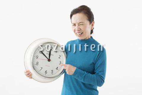 時計を指して苦い顔をするシニアの女性