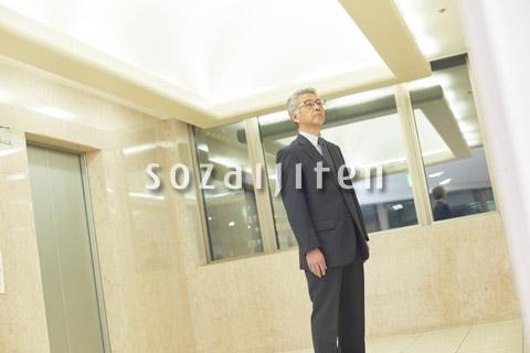 エレベーターを待つシニアのビジネスマン