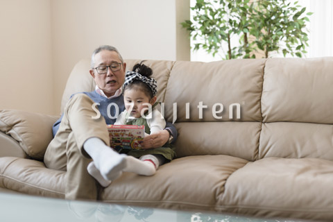 ソファーで孫と遊ぶおじいちゃん
