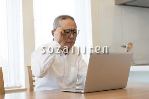 ノートパソコンを使うシニアの男性
