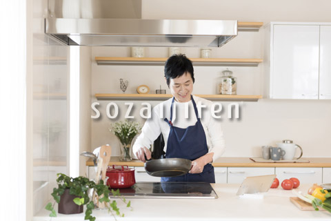 タブレットPCを見ながら調理しているシニアの女性