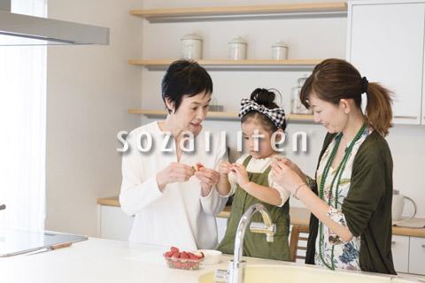 台所でイチゴを洗う孫と母と祖母