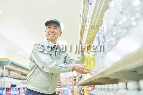 スーパーでマネージャーとして働くシニア男性(商品補充)