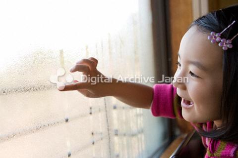 窓に絵を描く女の子