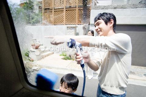 家の前で洗車をする父親と男の子