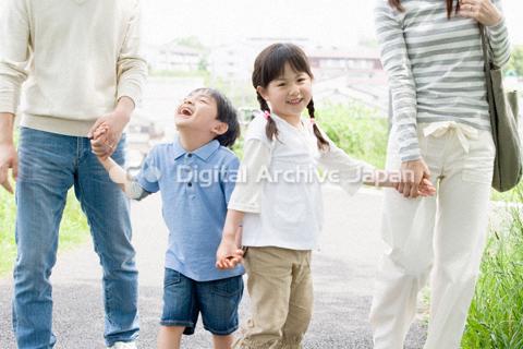 両親と手をつなぐ子供たち