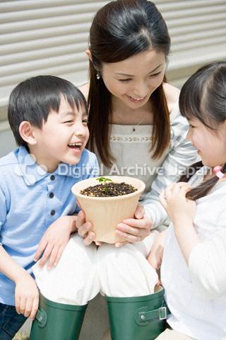 新芽を見る母親と子供たち
