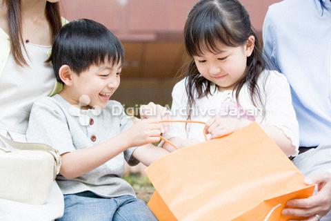 紙袋の中を覗く男の子と女の子