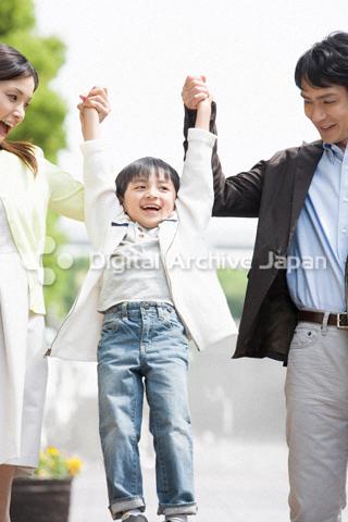 両親と手をつなぐ男の子