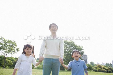 父親と手をつなぐ子供たち