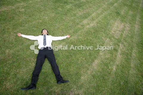 芝生の上に寝転がるビジネスマン