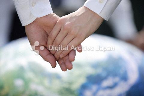 地球儀ボールの前で手を繋ぐ男女