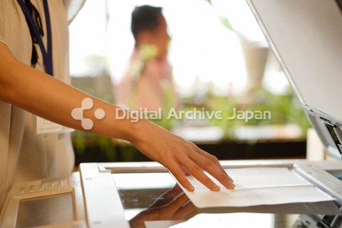コピー機でコピーをとる女性の手元