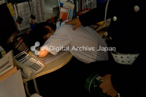 徹夜で作業をしている男性を起こす警備員