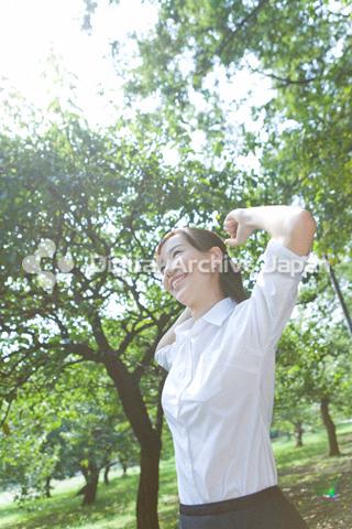 緑の中で背伸びをしている女性