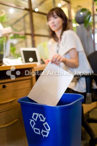 リサイクルBOXに紙を入れる女性