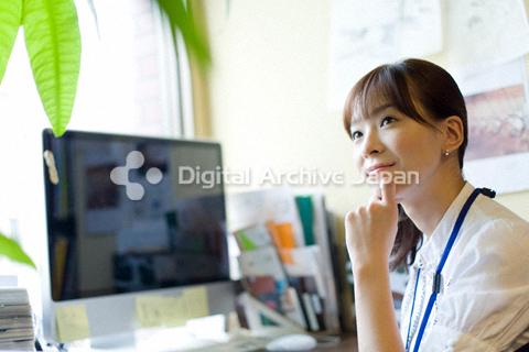 デスクに座って考える仕草をしている女性