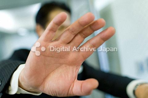 カメラのレンズを手で塞ごうとする男性