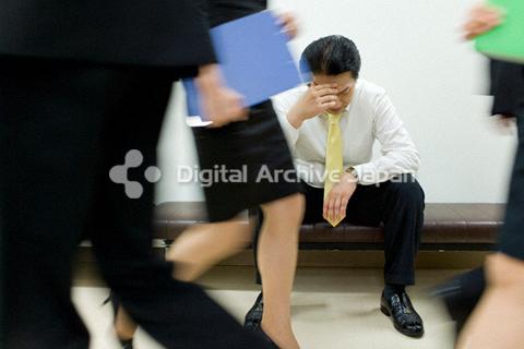 イスに座って頭を抱えるビジネスマン