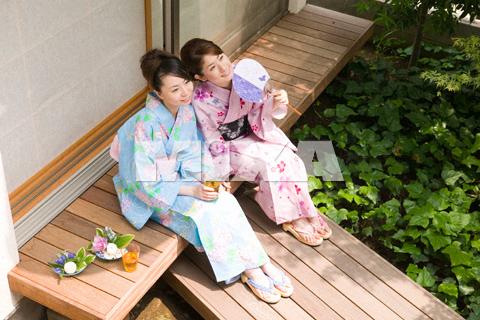 縁側でお茶を飲む浴衣姿の若い女性2人