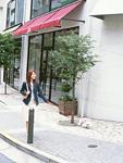 街角を歩く女性とミニチュアプードル