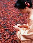 紅葉の落ち葉と着物の女性
