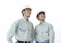 見上げる建設作業員