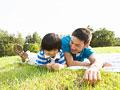 芝生に寝転ぶ父と息子