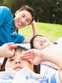 芝生に寝転ぶ家族