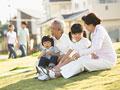 タイトル:芝生に座る祖父母と孫