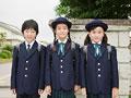 校門の前に並んで立つ小学生
