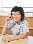虫眼鏡を覗く小学生